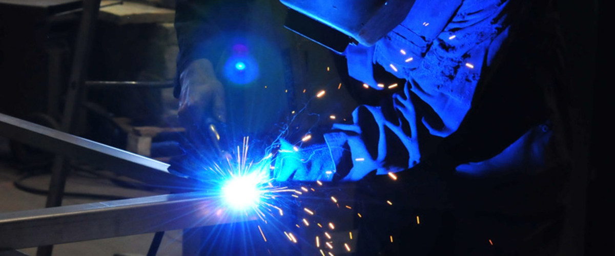 Sparks fly as welder works on metal.