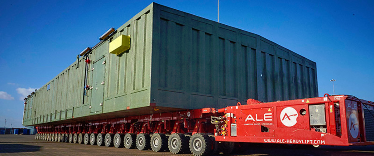 Large container being transported on heavy lifting vehicle.